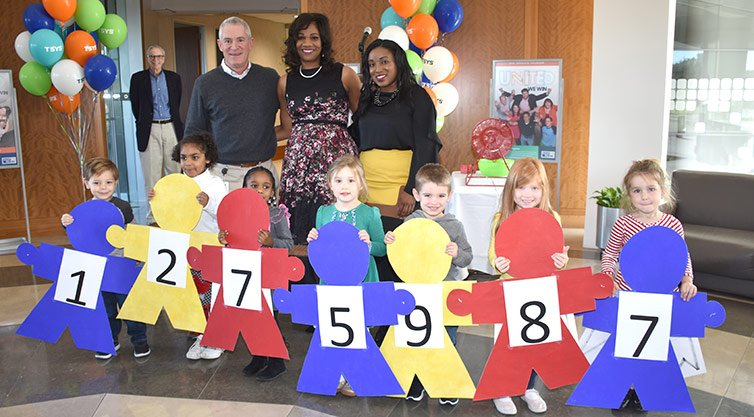 Children standing with TSYS team members as they reveal the 2018 campaign total of $1,275,987.
